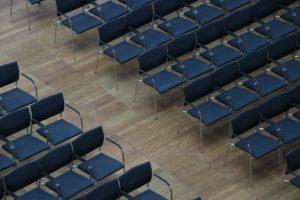 Leere Stühle in Konferenzsaal bei abgesagter Veranstaltung